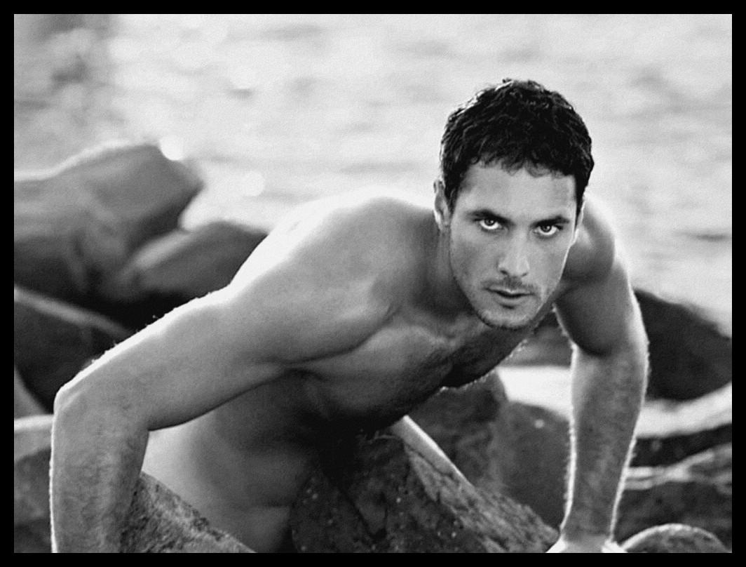 Une magnifique photographie en noir et blanc d'un homme nu posant sur des rochers