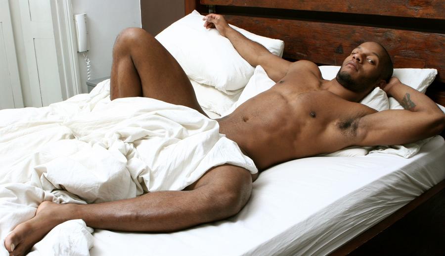 Magnifique métis tatoué nu dans son lit