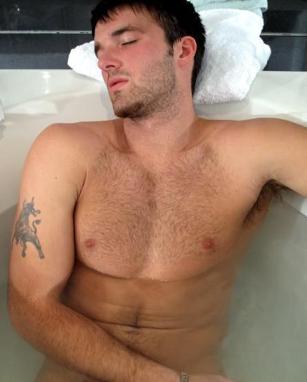 Un homme nu prend son bain