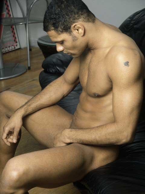Un homme nu, métis, musclé avec un tatouage sur le bras