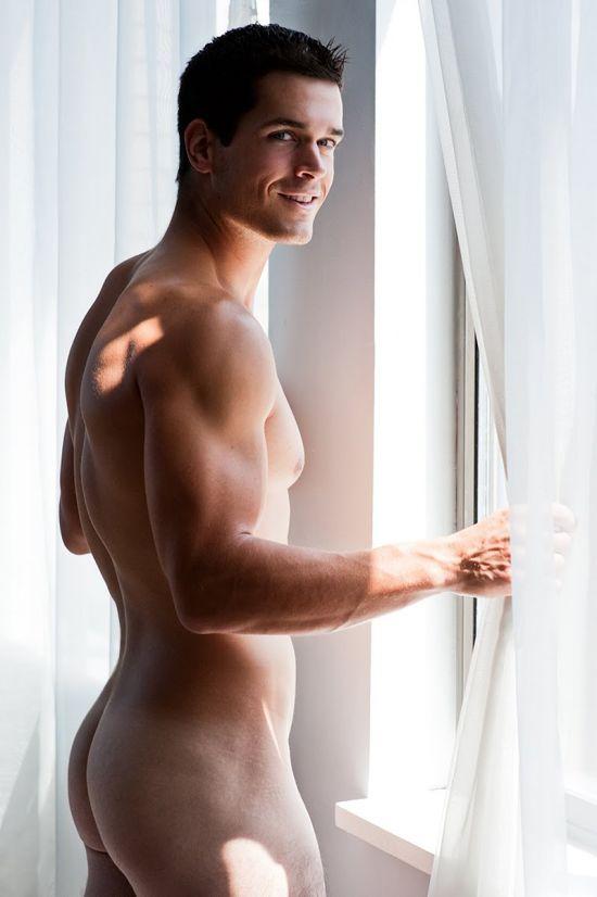 Un bel homme nu, souriant, debout, et de dos, qui nous montre de belles fesses bien rebondies