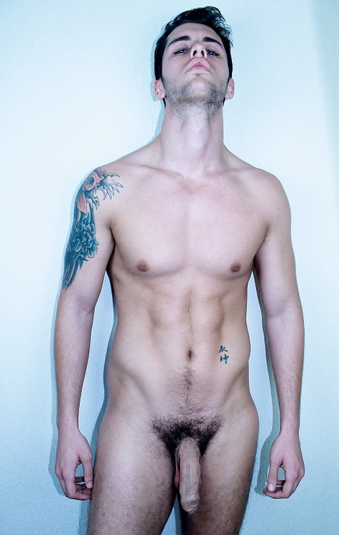 Un beau mec à poil, brun, tatoué et musclé.
