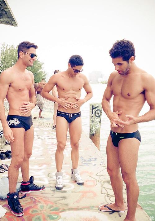 Trois hommes musclés presque nus sur les bors d'une rivière