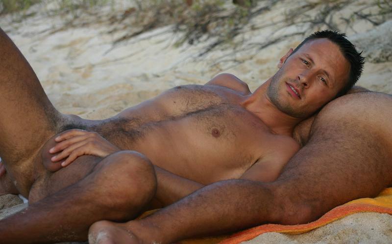 Une photo de deux hommes nus, poilus et souriants, sur une plage naturiste !