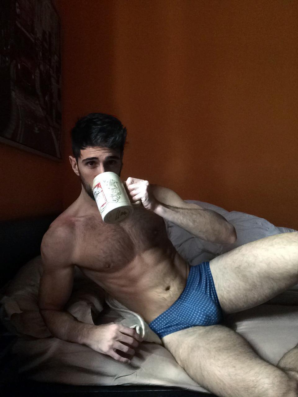 Cette photo d'homme presque nu est démente ! Le mec avec son gros bulge boit son café dans un lit