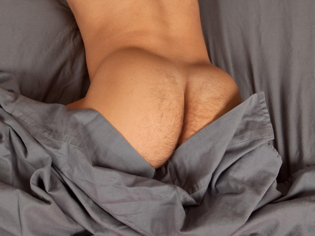 Un homme nu vous propose de découvrir de très belles fesses musclées, perdues dans des draps gris