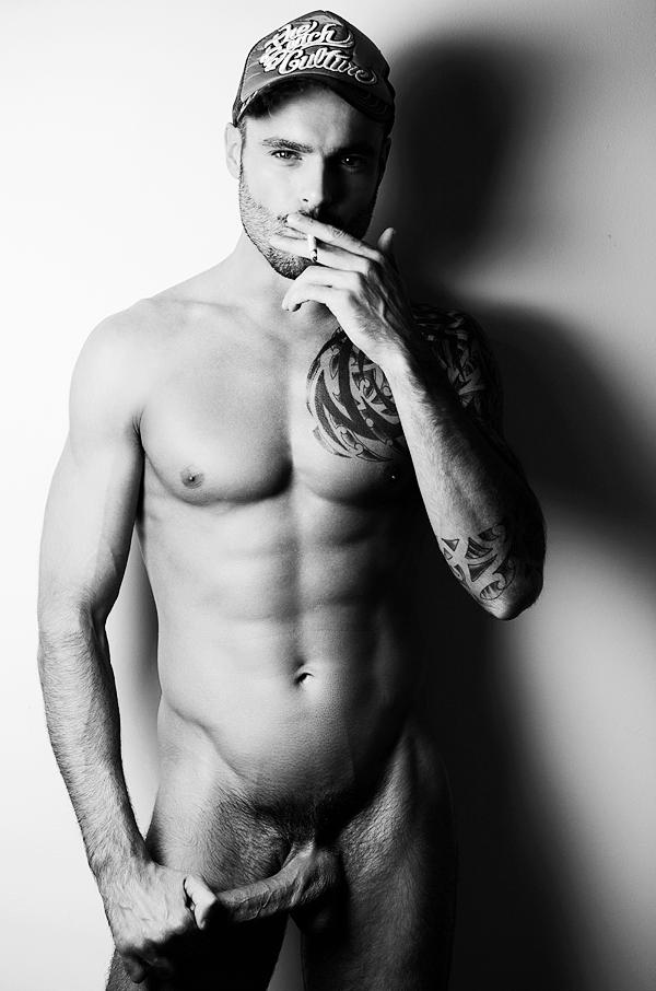 Photo d'un bel homme nu gay lascard avec une énorme bite. Il est tatoué et bien foutu, musclé et charmant.