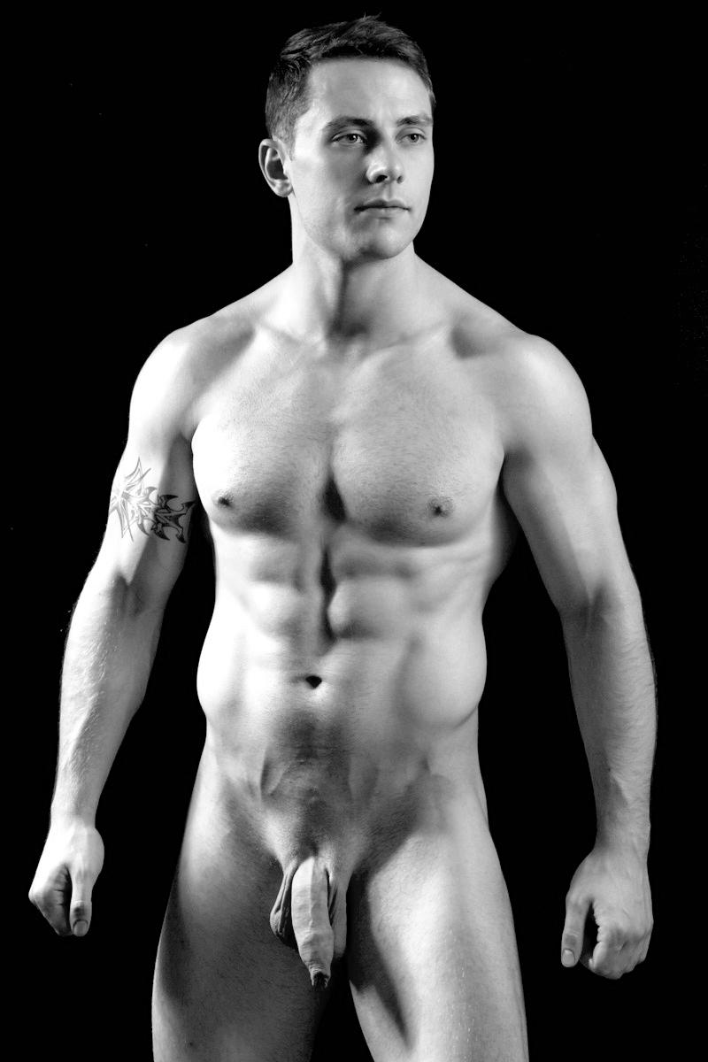 Photo d'un homme nu imberbe avec un très long prépuce et tatoué