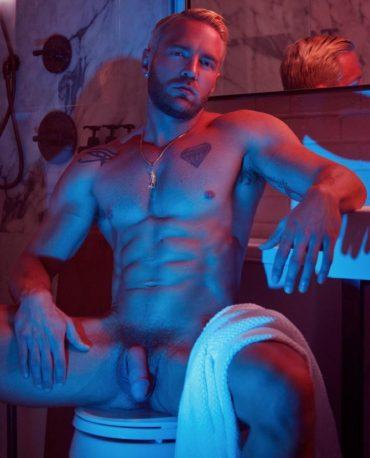 Modèle tatoué assis nu sous un éclairage rouge et bleu